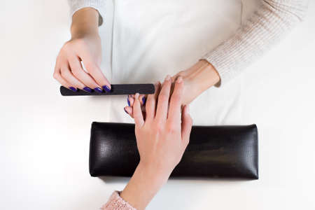 nail file: Top view manicurist at work nail file hand little finger of client.Hand on the black professional pillow. Stock Photo