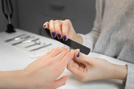 nailpolish: Manicure process with nail file in beauty salon. Manicure makes service beautiful girl client.On background are instruments manicure and pedicure. Stock Photo