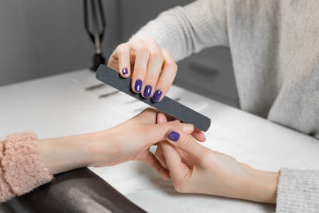 manicure and pedicure: Beautician filing female clients thumb and nails at spa beauty salon.Manicurist work on pure white table with professional tools for manicure and pedicure.