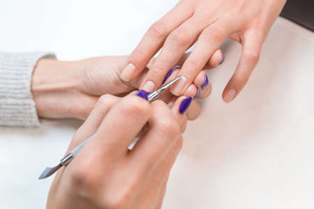 cuticle: Top view of manicurist removing cuticle from the nail clients girl ring finger at beauty salon. Hand lies on a glass white napkin.