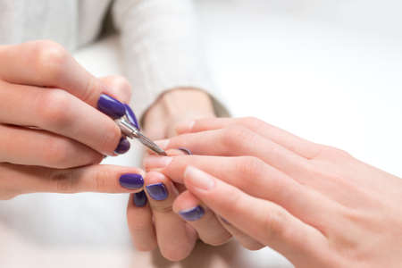 cuticle: Manicurist removing cuticle from ring finger of girl client at beauty salon. Manicurist work on pure white table with professional tools for manicure and pedicure.