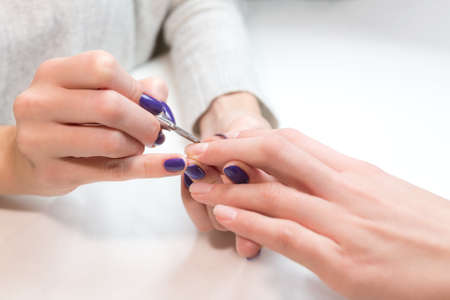 nailpolish: Closeup beautician remove cuticle from ring finger of client at beauty nail salon.Picture procedure in the process.