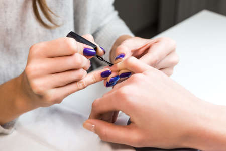 Manicurist putting black shellac on the fingernails of a lady client in a beauty salon with a small applicator. Master with beautiful blue shellac manicure.