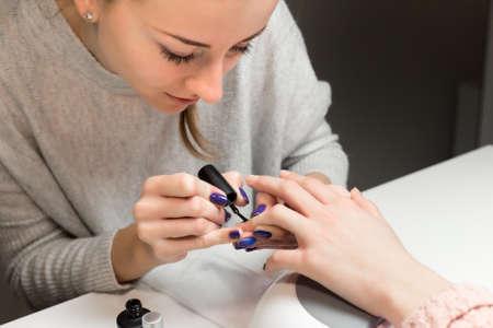 スパ サロンでマニキュアを行うためのプロセス。美容師は、美容サロンで爪に黒のマニキュアを適用します。手のケアの概念です。 写真素材