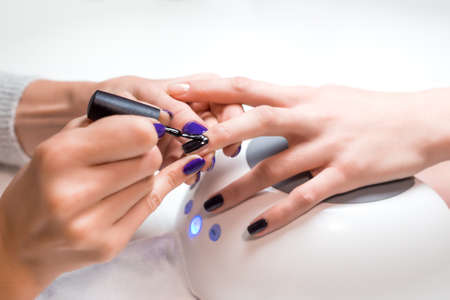 Closeup manicurist applies nail gel polish on middle finger. Girl client holds hand on the client on Uv lamp. Beautician gently manicured service. Stock Photo