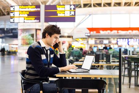 revisando documentos: Disparo de un hombre de negocios independiente guapo hablando por un teléfono móvil, mientras que la revisión de documentos sentados en el café aeropuerto fuera de la oficina. hombre de negocios usando la computadora portátil durante la hora del café.