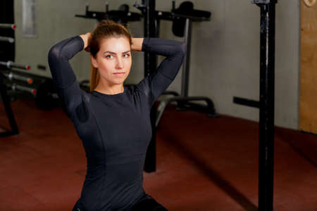 Lifestyle portrait of beautiful girl athlete on the mat.Attractive fitness woman, trained female body at the gym.
