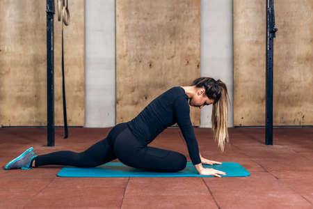 fit girl: Beautiful woman stretching legs in sports club on the green mat.Stretching young fitness girl in black sportswear.Lifestyle concept.