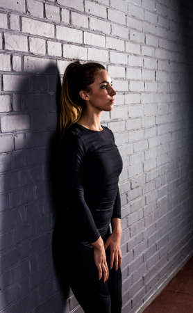 lean back: Beautiful girl athlete resting after a hard workout at the gym.Young woman lean back on a gray brick wall. Fitness girl in a black compression suit and in great shape. Stock Photo