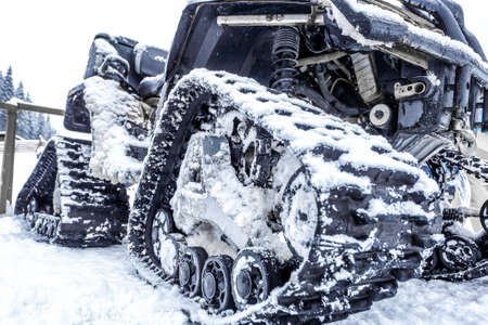 snowcat: Closeup of a caterpillar snowmobile with snow. Black truck of the snowcat.