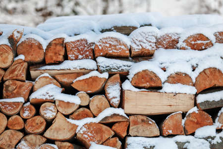 winter wood: Stacked firewood and covered with snow. The texture of wood, brown, nature, natural eco. Stock Photo