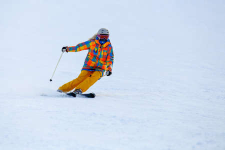 ski mask: Male skier skiing in fresh snow on ski slope on a sunny winter day at the ski resort. Skier in red ski suit and mask slides fast while skiing from slope. Stock Photo