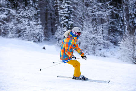 equipping: Young female ski rider in motion in winter mountains at ski resort. Man skier in a bright orange suit equipping and mask.