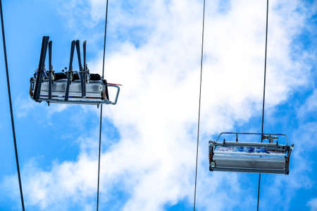 chair on the lift: Bottom view of pair of skiers on chair lift in vacation on the background of blue sky and white clouds in bright day sunday