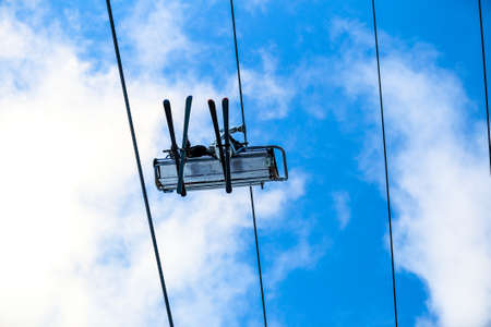 steel cable: Bottom view of skiers have a fun on chair lift in the sky and steel cable Stock Photo