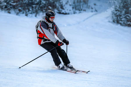 winter vacation: Male skier in red ski suit and mask slides down from the snow slope. Skier skiing downhill in high mountains against sunshine.