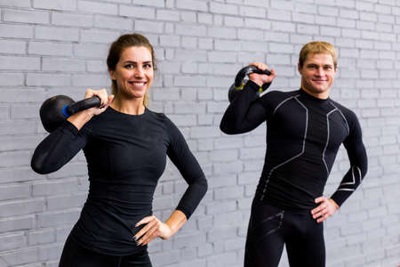 great suit: Handsome athletic young man with kettlebell in hand. Fitness instructor in black compression suit and in great shape on loft background looking intense at camera. Stock Photo