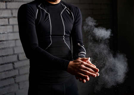 talc: Closeup handsome muscle young man applying chalk powder on dark background before deadlift barbells workout. Fitness instructor in black compression suit putting talc on his hands.