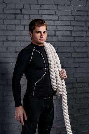 compression: Man with twisted sport rope on shoulder in gym and in black compression suite above grey wall