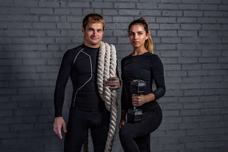 talc: Strong man holding  an sporty woman with twisted sport rope on shoulder and smiling girl with dumbbell Stock Photo