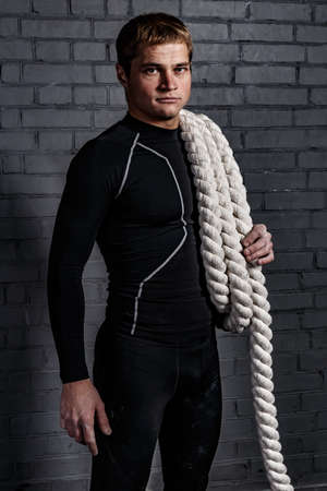 magnesia: Man with twisted sport rope on shoulder in gym and in black compression suite above grey wall