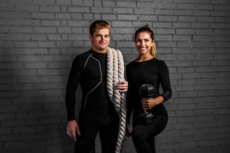 magnesia: Strong man holding an sporty woman with twisted sport rope on shoulder and smiling girl with dumbbell Stock Photo