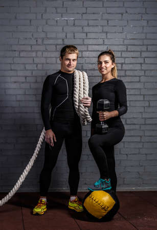 talc: Strong man holding an sporty woman with twisted sport rope on shoulder and smiling girl with dumbbell and put leg on the ball Stock Photo