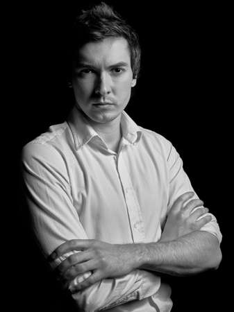 working model: Black and white portrait of a young businessman in a white shirt on a black background. Fashion model kind of guy. Stock Photo