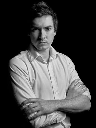 modelos hombres: retrato en blanco y negro de un joven hombre de negocios en una camisa blanca sobre un fondo negro. Moda tipo de modelo tipo. Foto de archivo