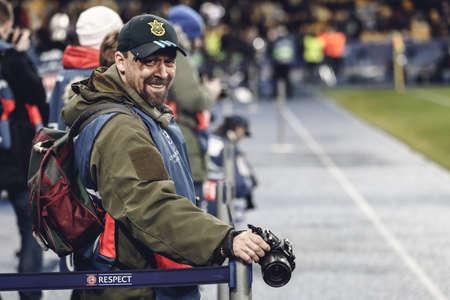 olimpiyskiy: KYIV, UKRAINE - FEBRUARY 24, 2016: UEFA Championes League game with Dynamo Kyiv and  Manchester City FC at NSC Olimpiyskiy stadium. Round of 16 - 1st leg. Photographer in the bib smiling and looking at the camera.