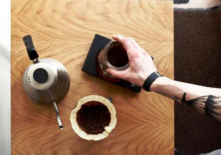 バリスタの手で上面にコーヒーを注ぐ