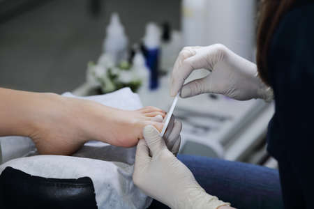 gash: Close-up gash nail file toenails in salon. The service is professional pedicure in the spa salon. Stock Photo