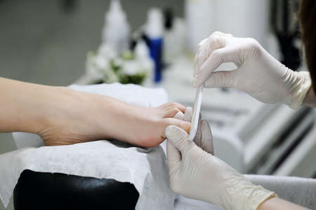 big toe: The big toe is doing pedicure nail file in salon. Manicurist in white mittens works with the client.