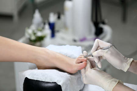 Woman receiving cuticle in manicure pedicure salon