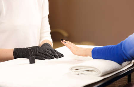 master: Finished customer manicure. Manicure master in black gloves does manicure Stock Photo