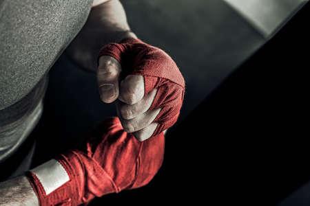 赤い包帯をボクシングとボクサーの男手をクローズ アップ。戦いまたはスポーツ ジムでトレーニングする前に戦闘機の拳。 写真素材