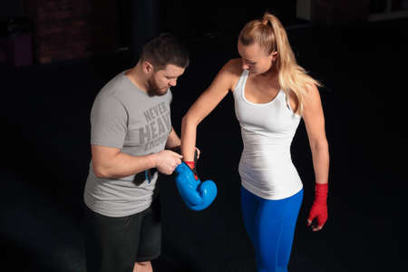 sports form: The coach puts on the boxing gloves girl before a workout in the gym. Beautiful girl in the sports form. Blue boxing gloves. Stock Photo