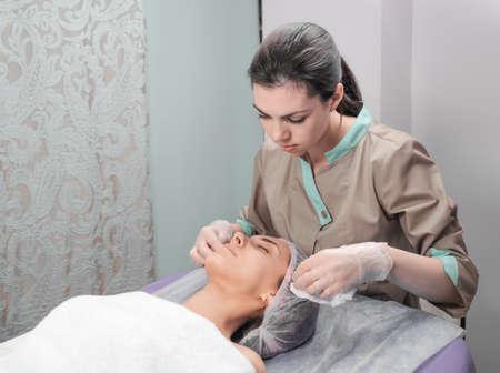 温泉療法により若い女性のビューティー サロンでフェイシャル マスクを受信します。美容師と美容サロンでフェイシャル マスクする前にクライア 写真素材