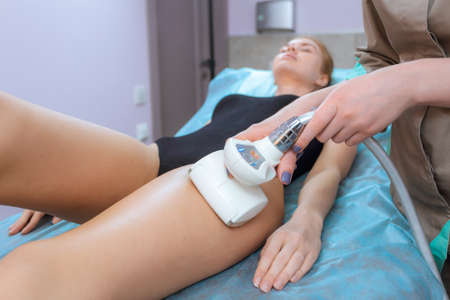 correction: Correction cellulite figures in the beauty salon. Girl makes a service in beauty clinic - vacuum massage and body correction. Young woman making a figure correction in a professional masseur.