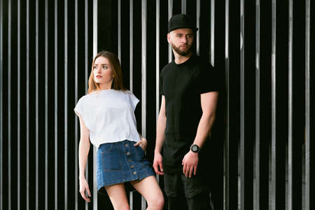 denim skirt: Stylish and fashionable couple posing on a background of a metal fence. Young man with a beard wearing a stylish black clothes. Beautiful fashionable girl in a denim skirt. Fashionable couple