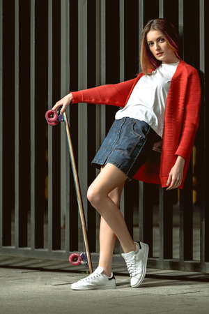 denim skirt: young woman with skateboard posing on a background of a metal fence. Beautiful girl in a stylish denim skirt and red sweater. Full body portrait of bearded stylish girl.