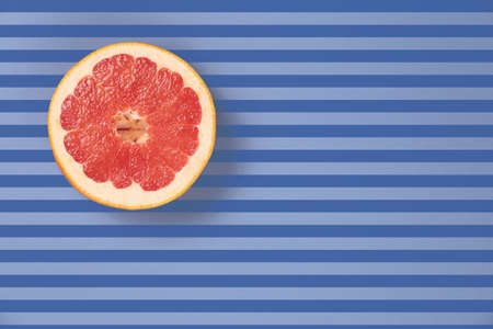 diagonal lines: Popart style  red juicy grapefruit on a striped background top view. Striped background in blue and dark blue stripes. Red grapefruit located top left. Lines texture. Diagonal lines.