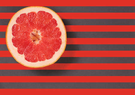 diagonal lines: Red juicy grapefruit on a striped background top view. Striped background in red and gray stripes. Red grapefruit located top left. Lines texture.  Diagonal lines. Stock Photo