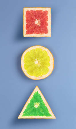Pop art view of various forms of grapefruit, which is painted in different bright colors. grapefruit looks like a traffic light on blue texture.
