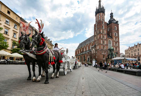 assumed: Krakow, Poland - May 25, 2016: ?oach on the main square near Church of Our Lady Assumed into Heaven. Is a Brick Gothic church rebuilt in the 14th century. With tourists on square