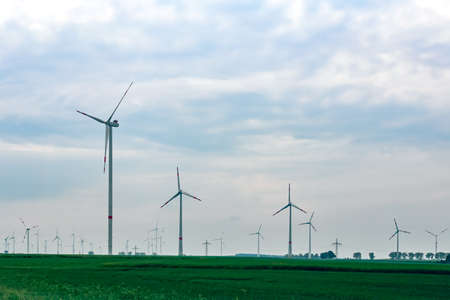 energy production: Lots of windmills on a green field.Windmills for electric eco power production.Big windmills for renewable electric energy production.