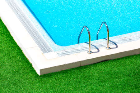 waterpool: Swimming pool with stair at hotel close up.Beautiful swimming pool with green grass around.Swimming pool with blue clear water.