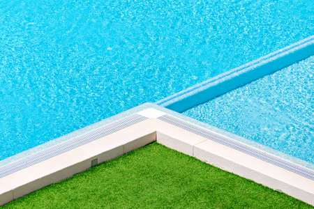 waterpool: Beautiful luxury Swimming pool resort hotel.Swimming pool and green grass ideal for backgrounds.Hotel swimming pool with sunny reflections close up view.