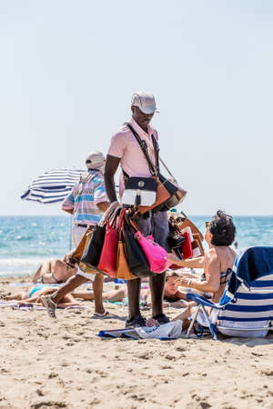immigrant: Alikante, Spain- June 4, 2016: An illegal immigrant, negro, from Africa sells fake bags on the beach in Spain Editorial