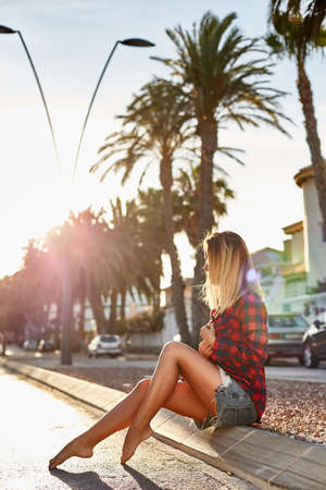 barefoot blonde: Young woman posing at sunset on the background of palm trees. Beautiful girl sitting on the curb in shorts and a red shirt. Barefoot blonde girl on the road.